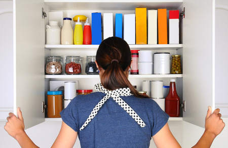 27716426 - a woman seen from behind opening the doors to a fully stocked pantry. the cupboard is filled with various food stuff and groceries all with blank labels. horizontal format, the woman is unrecognizable.