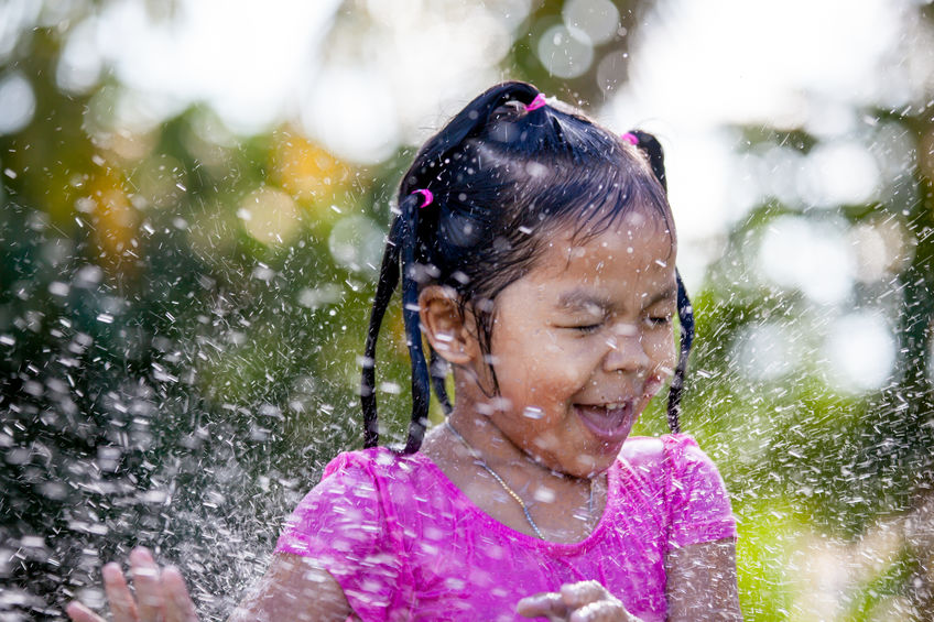 Cute asian child girl having fun to bath and playing water splas