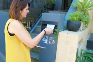 Anita Vitanova posting a note to a neighbour