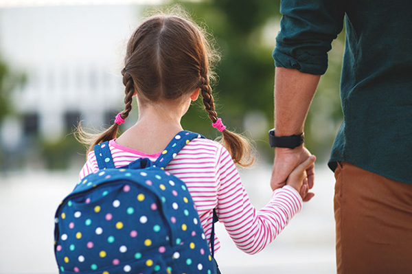 Young girl holding fathers hand