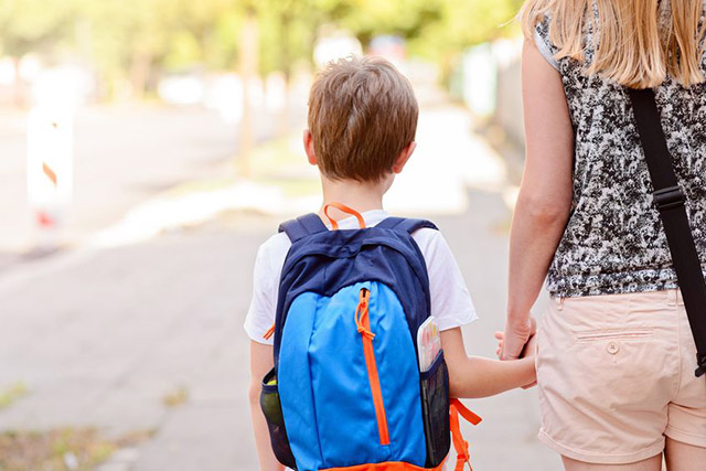 Boy starting School holding his mothers hand