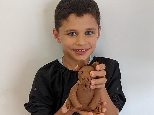 Kidz Artworx boy holding clay sculpture