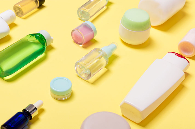 Composition of different sized cosmetic jars and bottles on yellow background. Beauty care concept with copy space
